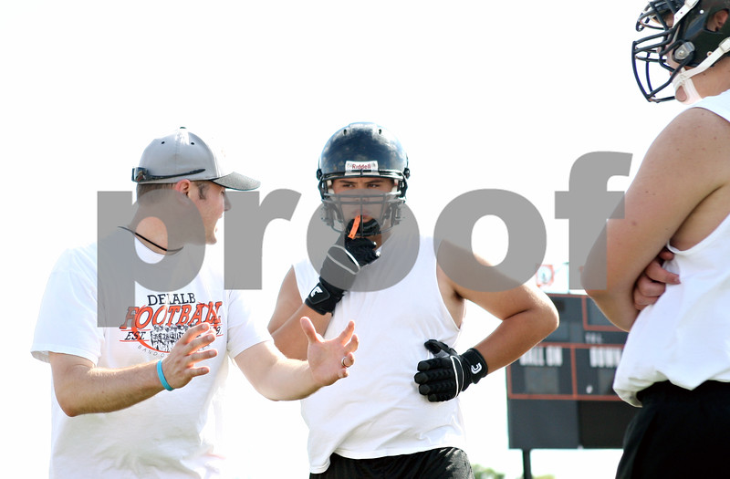 Rob Winner – rwinner@daily-chronicle.com<br /> <br /> Offensive line coach Dan Sanders (left) instructs Jake Smith during the first day of practice in DeKalb, Ill. on Wednesday, Aug. 10, 2011.