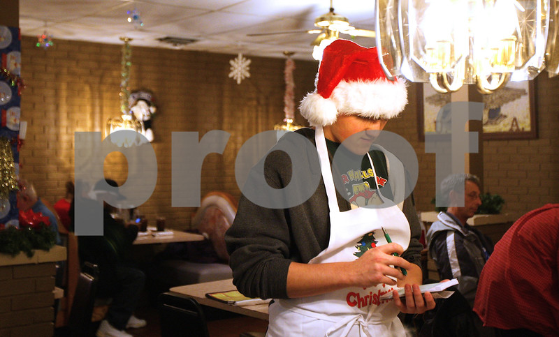 Kyle Bursaw – kbursaw@daily-chronicle.com<br /> <br /> Dylan Drake, 13, takes a table's order at Flippin Eggs during the restaurant's annual holiday dinner, where he  and his mother were volunteering.
