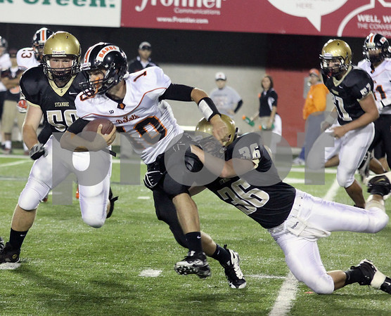Wendy Kemp - For The Daily Chronicle<br /> Sycamore's Scott Baker (36) tackles DeKalb quarterback Brian Sisler during Friday's game at Huskie Stadium.<br /> DeKalb 9/9/11