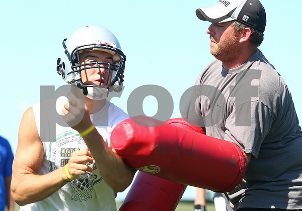 Kyle Bursaw – kbursaw@daily-chronicle.com<br /> <br /> Dylan Nauert maneuvers his way through the padded arms of coach Pat Ryan during a drill on Thursday, Aug. 11, 2011.