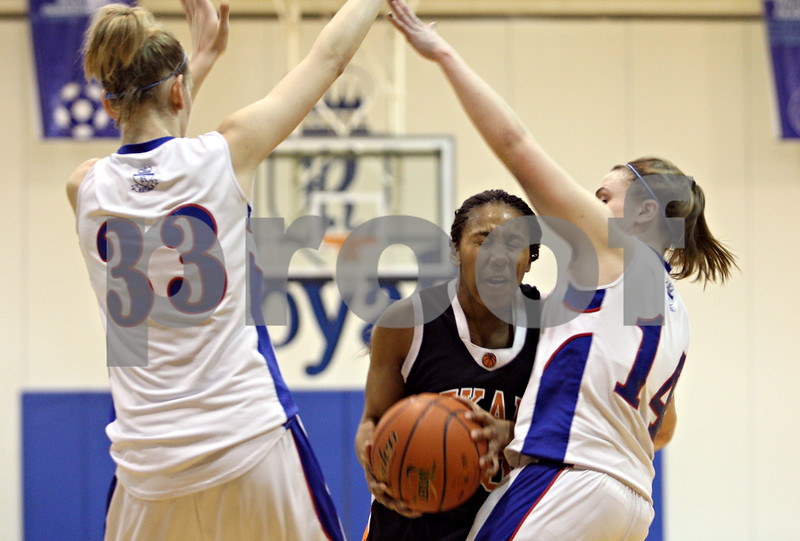 Rob Winner – rwinner@daily-chronicle.com<br /> <br /> DeKalb's Courtney Patrick (center) is fouled by Hinckley-Big Rock's Kaitlin Phillips (right) during the fourth quarter of their game in Hinckley, Ill., on Monday, February 7, 2011.