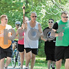 By CURTIS CLEGG<br /> cclegg@shawsuburban.com<br /> DeKalb police officer Fred Busby (center) carries the Special Olympics torch through Hopkins Park in DeKalb during the torch run from Sycamore to DeKalb on Sunday, June 5, 2011.  This is the 23rd torch run in which Busby has participated.