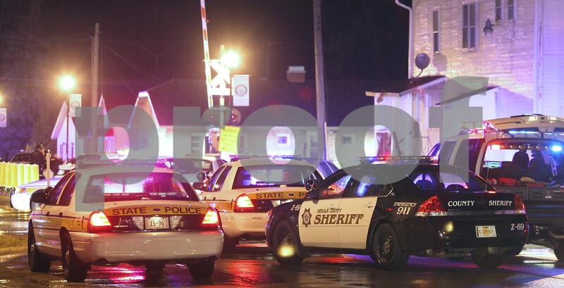 Kyle Bursaw – kbursaw@daily-chronicle.com<br /> <br /> More than a dozen law enforcement vehicles line South Somonauk Road near the railroad tracks in Cortland, Ill. on Thursday, July 21, 2011.