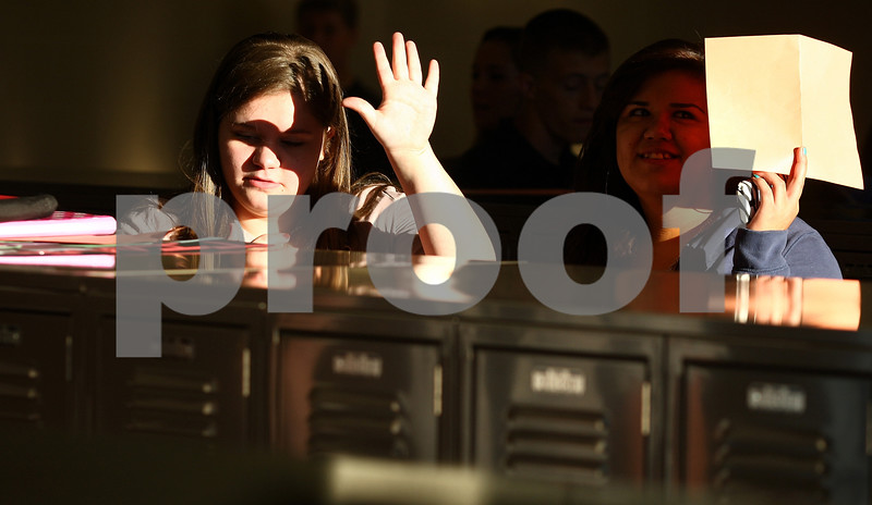 Kyle Bursaw – kbursaw@shawmedia.com<br /> <br /> Nora Hadji and another DeKalb High School student shield their eyes from the sun coming in the windows of the east locker bay on the first day of school on Tuesday, Sept. 6, 2011.