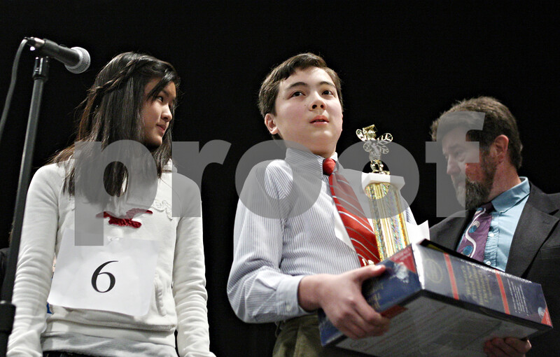 """Rob Winner – rwinner@daily-chronicle.com<br /> <br /> Angelina Ye (left), 12, who placed second in the DeKalb County Spelling Bee and first place speller Mark Rogers, 12, stand on stage to receive their awards on Saturday at Kishwaukee College. The winning word was """"mesmerize."""""""
