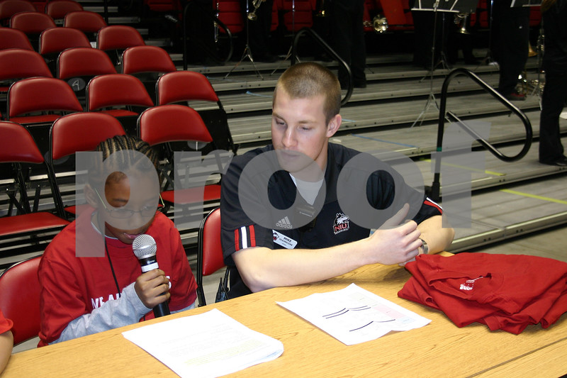 """Ian Harrison, 9, of DeKalb, shares information with the crowd at the Northern Illinois University women's basketball game Sunday at the Convocation Center. Harrison was a junior announcer as part of the """"Kids Take Over"""" event Sunday. The Huskies beat the Miami University RedHawks 71-64.<br /> <br /> Caitlin Mullen - cmullen@daily-chronicle.com"""