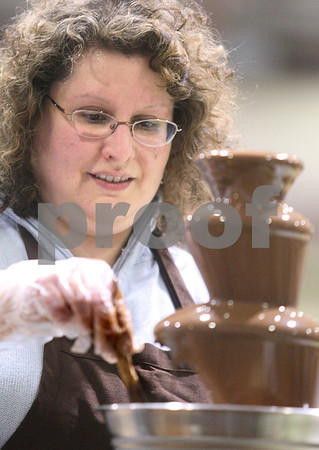 Kyle Bursaw – kbursaw@daily-chronicle.com<br /> <br /> Chocolatescapes owner Nancy DeRaedt dips pretzel sticks in a chocolate fountain for visitors of the Community Expo to taste. The expo was held at Sycamore high school on Tuesday, March 22, 2011.