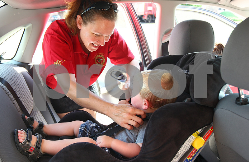 Kyle Bursaw – kbursaw@daily-chronicle.com<br /> <br /> Trooper Michelle Kistulinec inspects the positioning of the car seat straps on Brady Moris in the parking lot of Jewel in DeKalb, Ill. on Friday, July 15, 2011.
