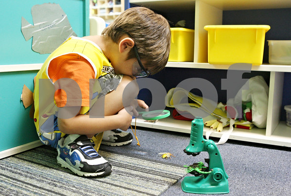 Rob Winner – rwinner@daily-chronicle.com<br /> <br /> 4-year-old Gabriel Escobar uses a magnifying glass to observe a plastic insect at Once Upon a Child Care in Sycamore on Monday afternoon.