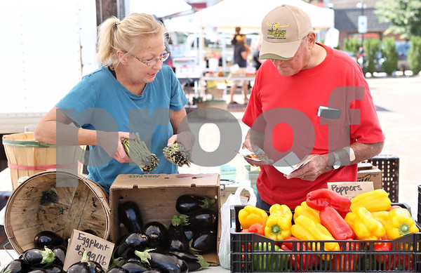 Rob Winner – rwinner@daily-chronicle.com<br /> <br /> Daryl Srail (left), of Windy Acres Farm, gets two bunches of asparagus ready for Bernard W. Parsley, who paid with fruit and vegetable vouchers at the DeKalb Farmers Market on Thursday afternoon.