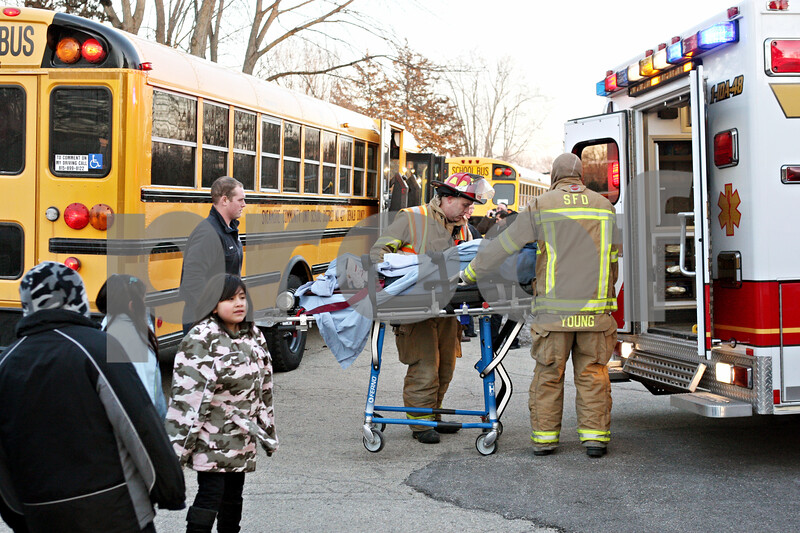 Rob Winner – rwinner@daily-chronicle.com<br /> <br /> A third student is taken off a Sycamore school bus on a stretcher by emergency personnel after an accident in front of Evergreen Village in Sycamore on Tuesday afternoon.