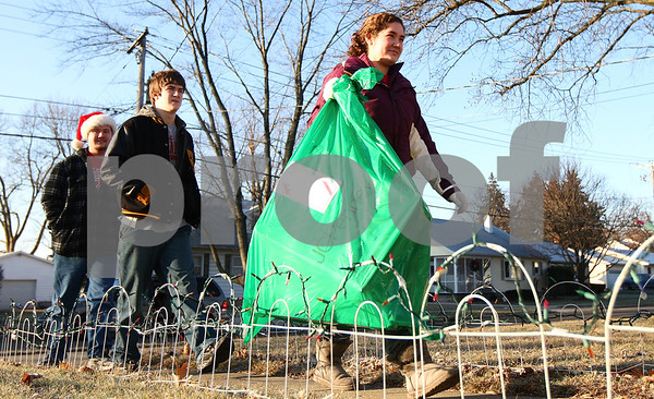 Kyle Bursaw – kbursaw@shawmedia.com<br /> <br /> Kaitlyn King, 18, followed by her brothers Dustin, 16, and Daniel, 21,<br /> bring a gift bag to a Sycamore home on Saturday, Dec. 24, 2011. The three Kings, accompanied by their parents, delivered gifts to four families while volunteering with Goodfellows of DeKalb-Sycamore.