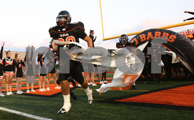 Kyle Bursaw - kbursaw@shawmedia.com<br /> <br /> DeKalb's Jake Smith leads the Barbs out of the tunnel in their home opener against Galesburg on Friday, Aug. 24, 2012.
