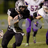 Karen Naess For The Chronicle<br /> <br /> Kaneland's Jesse Balluff runs with the ball as Belvidere's Jacob Fondrk looks to make the stop in playoff play on Saturday at Kaneland.