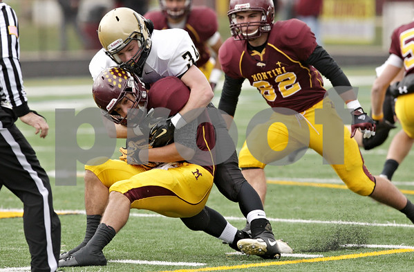 Rob Winner – rwinner@shawmedia.com<br /> <br /> Montini quarterback Mark Gorogianis (2) is tackled by Sycamore linebacker Jack Dargis (34) for an 8-yard loss in the first quarter of a Class 5A playoff game in Lombard, Ill., Saturday, Nov. 3, 2012. Montini defeated Sycamore, 24-22.