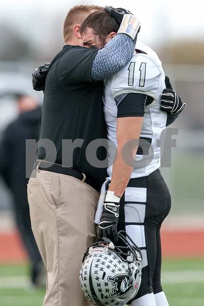 Sean King for the Chronicle<br /> <br /> Kaneland's Zack Martinelli (11) is consoled by assistant coach Keith Snyder after suffering a season ending loss to Lincoln-Way West during a Class 5A playoff game in New Lenox, Ill., on Saturday, Nov. 3, 2012. Lincoln-Way West defeated Kaneland, 31-15.