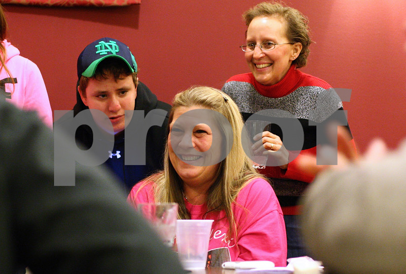 Kyle Bursaw – kbursaw@shawmedia.com<br /> <br /> Dawn Weber (center), cracks a smile on Wednesday while talking to friends and family, including her cousins Brett and Lisa Dienst (left and right), during a community meal at Feed 'Em Soup honoring Dawn's daughter Lexi Weber and boyfriend Tim Getzelman, who died in a fatal car accident a year ago.<br /> <br /> Wednesday, Feb. 29, 2012.