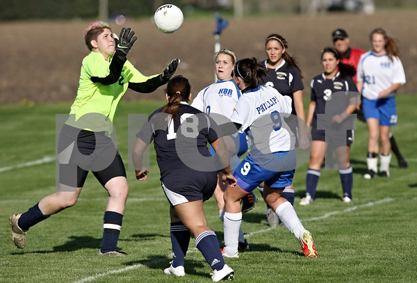 Rob Winner – rwinner@shawmedia.com<br /> <br /> Hiawatha goalkeeper Randi Maynard (left) looks to control a ball in front of the Hawks' goal during the first half in Hinckley Friday. H-BR defeated Hiawatha, 4-0. Phillips scored three goals for the Lady Royals.