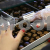 Kyle Bursaw – kbursaw@shawmedia.com<br /> <br /> Kim Stafford, an employee at the Confectionary in DeKalb, assembles a custom box for a customer as he makes his selections on Thursday, Feb. 9, 2012.
