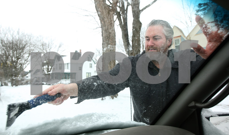 Kyle Bursaw – kbursaw@shawmedia.com<br /> <br /> DeKalb resident Tony Sharp clears the snow and ice from his windshield Friday afternoon on Second Street.<br /> <br /> Friday, Jan. 13, 2012.