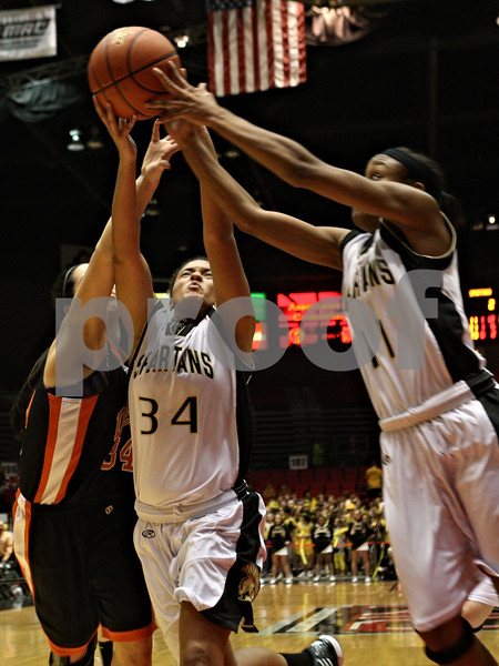 Rob Winner – rwinner@shawmedia.com<br /> <br /> DeKalb's Rachel Torres (from left to right), Sycamore's Olyvia Rand and Lake Kwaza go up for a rebound under the Barbs' basket late during the fourth quarter. DeKalb defeated Sycamore, 39-37, on Friday night at the Convocation Center in DeKalb.