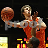 Rob Winner – rwinner@shawmedia.com<br /> <br /> DeKalb's Brian Sisler (10) goes to the basket over Sycamore's Rashaud Bomar during the third quarter. DeKalb defeated Sycamore, 57-41, at the Convocation Center in DeKalb on Friday night.