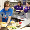 Kyle Bursaw – kbursaw@shawmedia.com<br /> <br /> Volunteer Brooke Wilson puts finished plates onto a tray for a server in the kitchen of the Feed 'Em Soup headquarters in DeKalb, Ill. on Wednesday, Feb. 29, 2012 during a community meal honoring Lexi Weber and Tim Getzelman.
