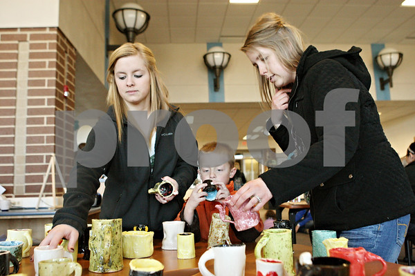 Rob Winner – rwinner@shawmedia.com<br /> <br /> (From left to right) Alexis Hardt, 16, Donnie Hardt, 5, and their mother Kelly Hardt look over mugs for sale made by Genoa-Kingston students in their art fundamentals class. Profits made by the sale will be split between the art department and Hope Haven.