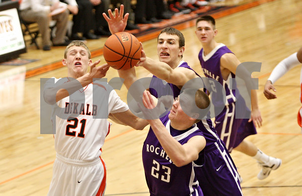 Rob Winner – rwinner@shawmedia.com<br /> <br /> DeKalb's James Robinson (from left to right), Rochelle's David Newton and Matt Rosenwinkel attempt to control a rebound under the Barbs' basket during the first quarter in DeKalb on Friday, Feb. 17, 2012. DeKalb defeated Rochelle, 69-67.