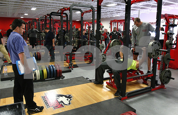 Kyle Bursaw – kbursaw@shawmedia.com<br /> <br /> A scout from the Indianapolis Colts (left) watches as former Northern Illinois linebacker Pat Schiller benches in the weight room of the Yordon Center during the NIU Pro Day on Friday, March 9, 2012.