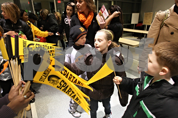 Rob Winner – rwinner@shawmedia.com<br /> <br /> Abi Payne, 8, reaches for a Sycamore Spartans flag upon entering the Convocation Center in DeKalb before the start of the DeKalb and Sycamore basketball games on Friday night.