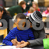 Kyle Bursaw – kbursaw@shawmedia.com<br /> <br /> Amiel Walker, 6, gets a little help from his mom, Melanie Fulton, while making a book about winter during an evening activity at Founders Elementary on Friday, Feb. 3, 2012.