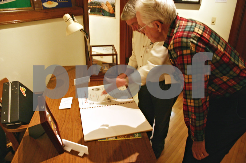 ANDREW MITCHELL — amitchell@shawmedia.com<br /> DeKalb Area Agricultural Heritage Association members Emerson Wells (left) and Allan Aves go through an album of DeKalb Ag dealer recruitment literature Sunday during an exhibition opening at the Nehring Gallery in DeKalb.