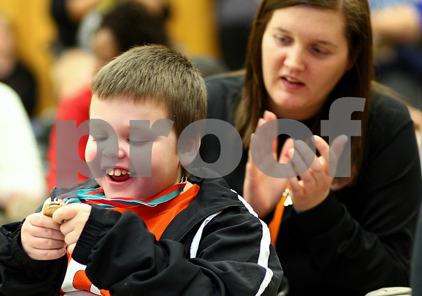 Kyle Bursaw – kbursaw@shawmedia.com<br /> <br /> Daniel Plowman, 8, smiles as he takes a look at his gold medals from the both the area and state Winter Special Olympics as Amy Drafke, one of his coaches, applauds during a presentation at Camelot DeKalb on Wednesday, Feb. 8, 2012.