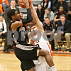 Rob Winner – rwinner@shawmedia.com<br /> <br /> Kaneland's Marcel Neil (23) is fouled by DeKalb's Jake Carpenter before scoring two during the second quarter in DeKalb on Friday, Feb. 10, 2012. Kaneland defeated DeKalb, 65-55.