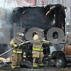 Kyle Bursaw – kbursaw@shawmedia.com<br /> <br /> Maple Park firefighters hose down beneath the hood of a pick-up truck while putting out the last of a fire that started in a camper and spread to the truck at a farm on County Line Road just north of Highway 64 on Monday, Jan. 9, 2012.