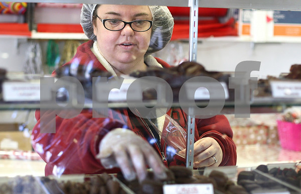 Kyle Bursaw – kbursaw@shawmedia.com<br /> <br /> Confectionary co-owner Betsy Hendrey bags up chocolates selected by a customer at their DeKalb location on Thursday, Feb. 9, 2012.