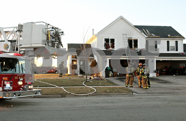 Rob Winner – rwinner@shawmedia.com<br /> <br /> DeKalb firefighters gather outside a townhouse located on the 2100 block of Eves Circle West in DeKalb after extinguishing a fire on Thursday.