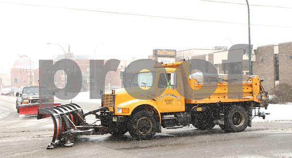 Kyle Bursaw – kbursaw@shawmedia.com<br /> <br /> A city of Sycamore plow works to clear the streets as another plow waits at the stop sign at the intersection of West Elm and South Main on Thursday, Jan. 12, 2012.