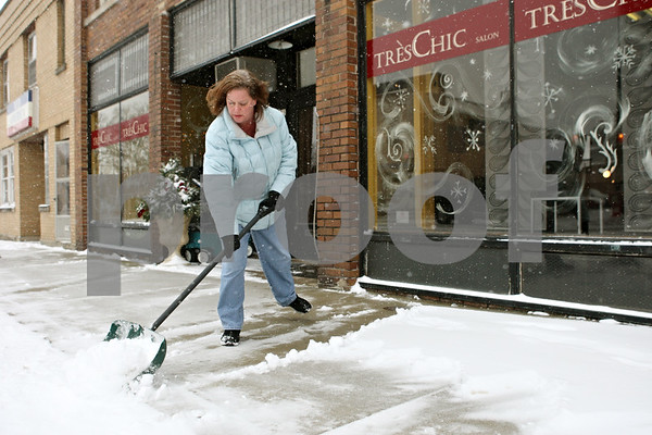 Rob Winner – rwinner@shawmedia.com<br /> <br /> Très Chic owner Robin Chuk clears away the snow from the front of her Hinckley business with a shovel on Thursday, Jan. 12, 2012.
