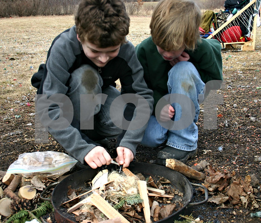 Aidan Bengford (right) and Bradley McKendry, both of Cub Scout Pack 133 in DeKalb, try to build a fire using flint Saturday, Feb. 4, 2012.<br /> <br /> By Nicole Weskerna - nweskerna@shawmedia.com