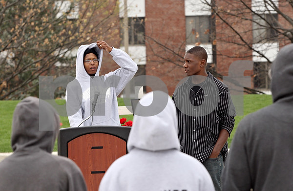 Rob Winner – rwinner@shawmedia.com<br /> <br /> Nina Cunningham pulls up the hood of her sweatshirt as her son Malique Cunningham, 15, watches during a rally to show support for Trayvon Martin at the Martin Luther King Commons at Northern Illinois University in DeKalb Friday. After the rally participants walked to DeKalb High School.