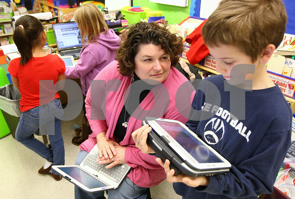 Kyle Bursaw – kbursaw@shawmedia.com<br /> <br /> West Elementary teacher Jennifer McCormick listens to a question from second-grader Beau Cash while two students in the background use an online dictionary to look up words on Thursday, Jan. 26, 2012. Each student in McCormick's nearly paperless classroom has a hybrid tablet laptop computer.