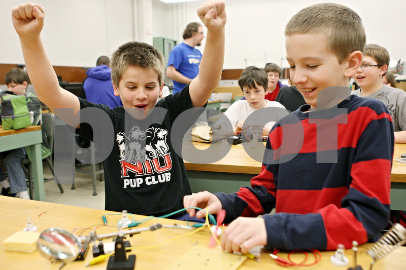 Rob Winner – rwinner@shawmedia.com<br /> <br /> Carter Maxwell, 11, reacts as Rory Martin, 11, holds a small fan that begins functioning using a battery pack during a hands-on basic circuitry class presented by the Northern Illinois University STEM Outreach program on Saturday morning on the NIU campus in DeKalb. STEM stands for science, technology, engineering and math. Maxwell and Martin both attend Founders Elementary School in DeKalb.