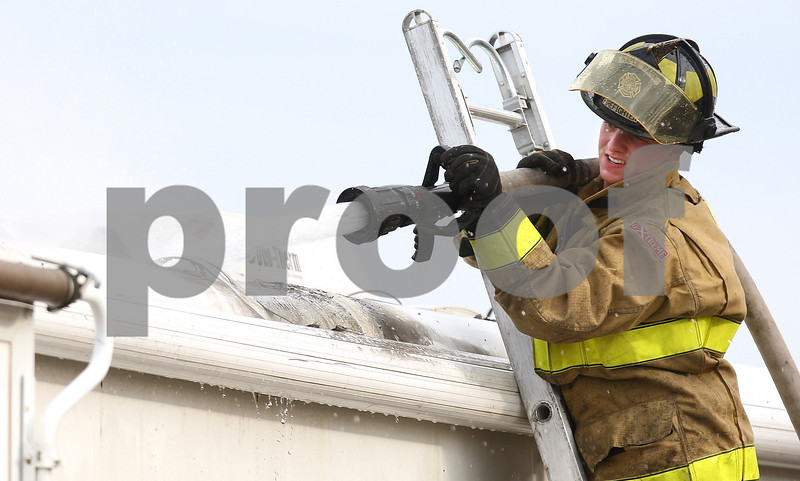 Kyle Bursaw – kbursaw@shawmedia.com<br /> <br /> Maple Park Firefighter Brent Miller hoses down a fire in a camper from above on Monday, Jan. 9, 2012.