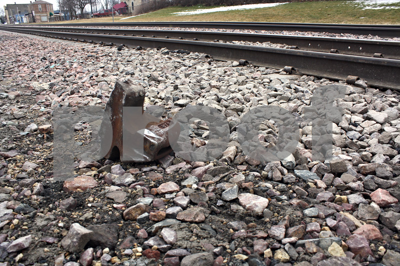 ANDREW MITCHELL — amitchell@shawmedia.com<br /> A piece of the broken railcar coupling sits along the train tracks Wednesday in downtown DeKalb. Officials say it was part of the reason a frieght train stalled on the tracks Wednesday morning.