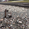 ANDREW MITCHELL— amitchell@shawmedia.com<br /> A piece of the broken railcar coupling sits along the train tracks Wednesday in downtown DeKalb. Officials say it was part of the reason a frieght train stalled on the tracks Wednesday morning.