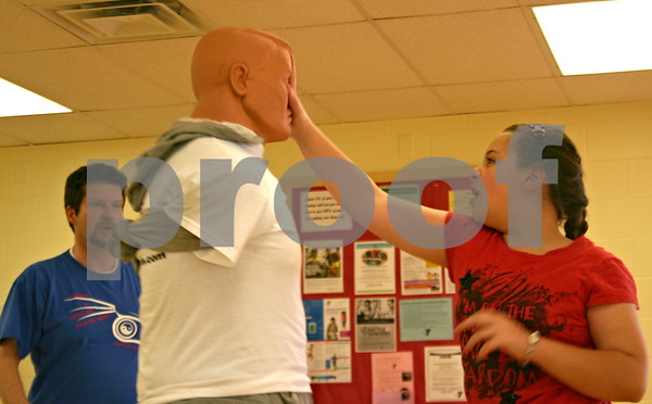 "Tess Moreno, 9, of DeKalb, practices hitting a mannequin and saying ""no"" during a bully prevention workshop held Sunday at the Kishwaukee Family YMCA in Sycamore. Instructor Tom Scott, left, taught the class aimed at children ages 5 to 14.<br /> <br /> By Nicole Weskerna - nweskerna@shawmedia.com"