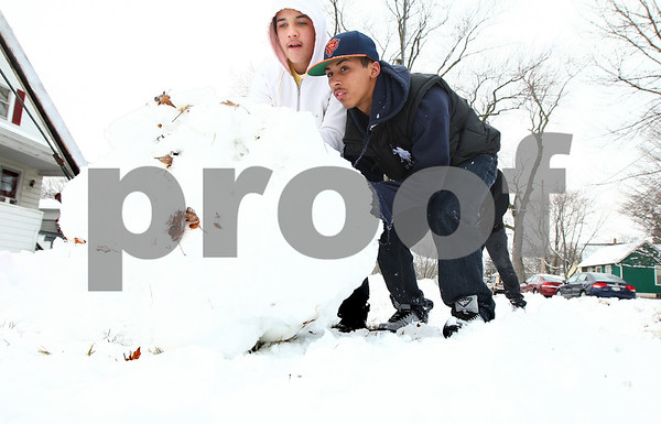 Kyle Bursaw – kbursaw@shawmedia.com<br /> <br /> Brandyn Rosario (left), 15, and his nephew Nicholas Rosario, 17, roll a large snowball Friday afternoon in DeKalb, Ill. The pair were off of school as a result of the snow.<br /> Friday, Feb. 24, 2012