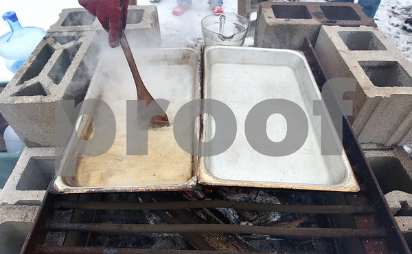 Kyle Bursaw – kbursaw@shawmedia.com<br /> <br /> J.T. Anesi stirs two trays of sap, the tray on the left had already been reducing for hours and the tray on the right had just started. The sap reduces into syrup at about a forty-to-one ratio according to Anesi, who was volunteering at Maple Syrup Fest on Saturday, March 3, 2012 at the Russell Woods Forest Preserve in Genoa, Ill.